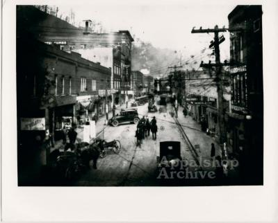 A town [Hazard] street filled with people, horses, and cars