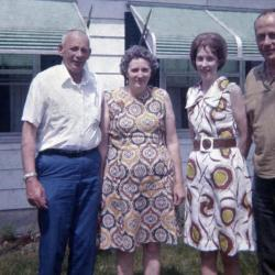 Two men and two women standing in front of a white house